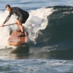 Dropping in on a head high wave with a Sawyer Wooden SUP