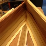 Displacement hull nose construction on wooden SUP.