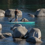 Walking the deck of a wooden SUP for a pivot turn between boulders at Lake Tahoe.